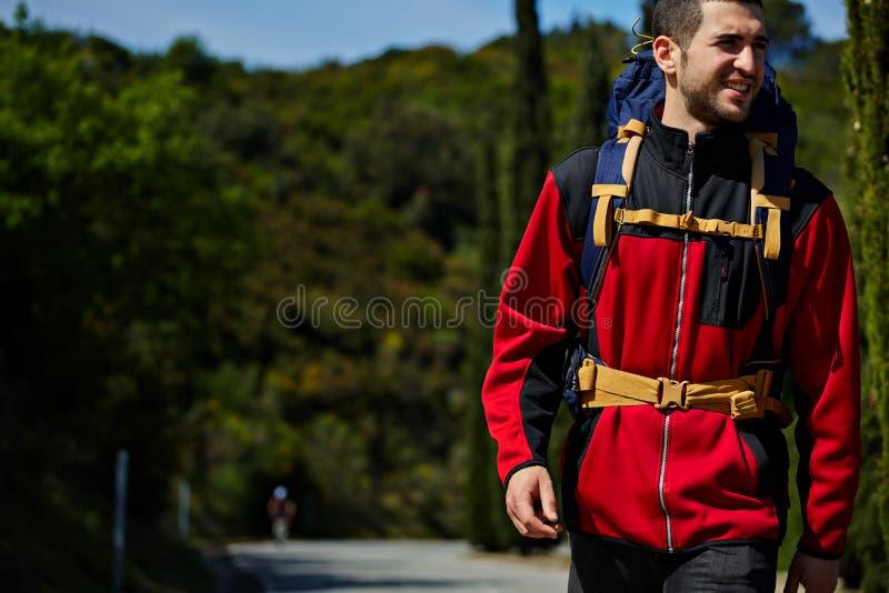 Красивый молодой hiker с рюкзаком идет на дезертированную дорогу и усмехаться в горах стоковые изображения rf
