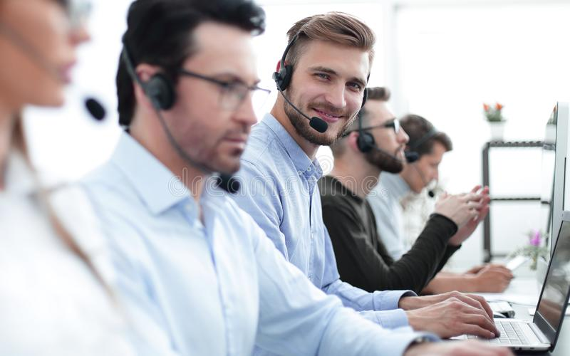 Красивый мужской оператор телефона работы с клиентом при шлемофон работая в центре телефонного обслуживания стоковые фото