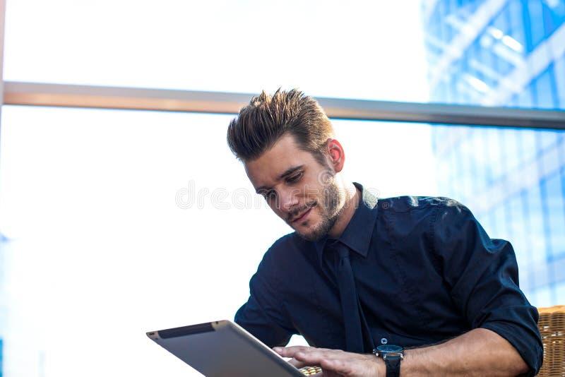 Красивый мужской работодатель используя посыльного на сенсорной панели во время перерыва работы в компании стоковое изображение