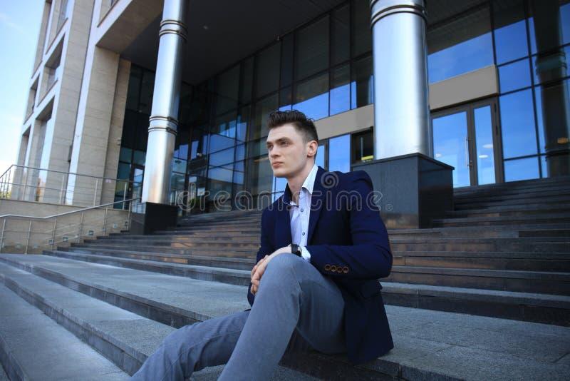 Красивый мужской руководитель бизнеса сидя на лестницах вне здания стоковые изображения