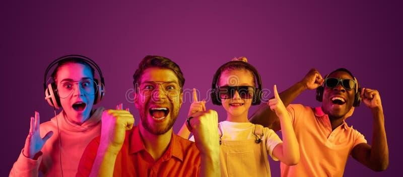Красивый мужчина и женские модели в неоновом свете изолированном на пурпурной предпосылке студии стоковые фото