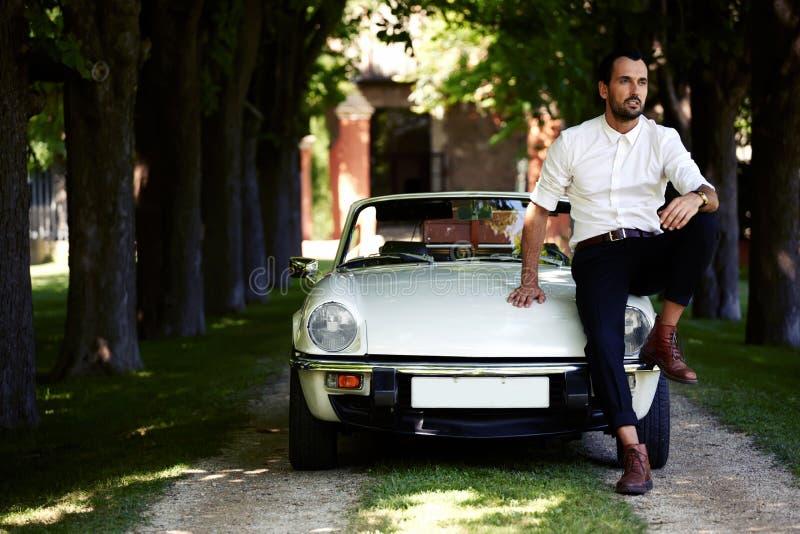 Красивый мужчина смотрит чудесное усаживание на клобуке роскошного автомобиля cabriolet против его виллы на сельской местности стоковая фотография rf