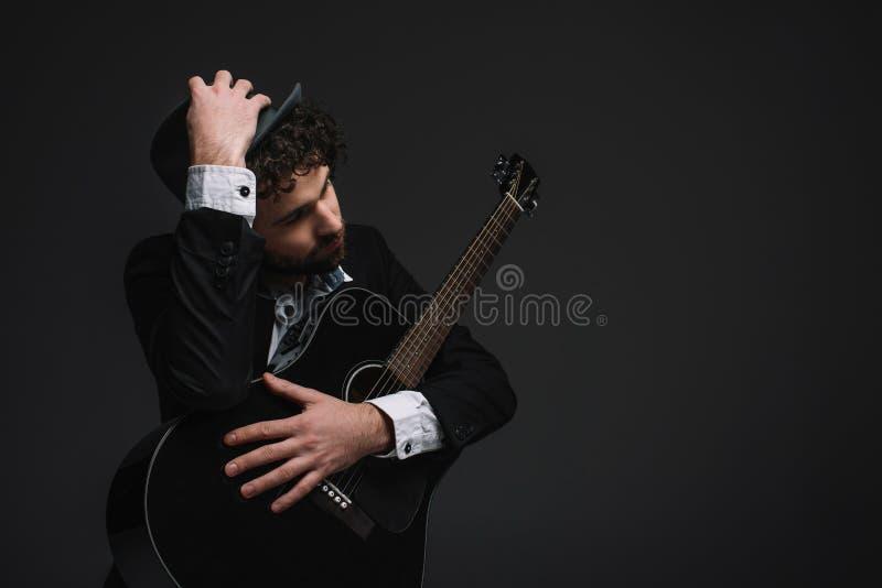 красивый музыкант в шляпе обнимая его гитару стоковая фотография rf