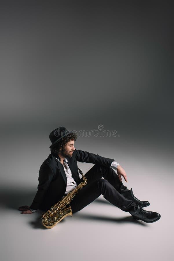 красивый музыкант сидя на поле стоковая фотография