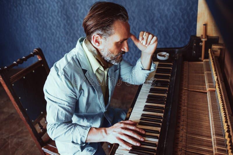 Красивый музыкант составляет усаживание музыки на рояле стоковое фото