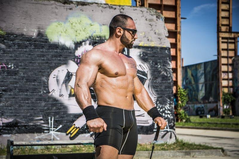 Красивый мышечный без рубашки человек толстого куска на открытом воздухе в установке города стоковое фото rf