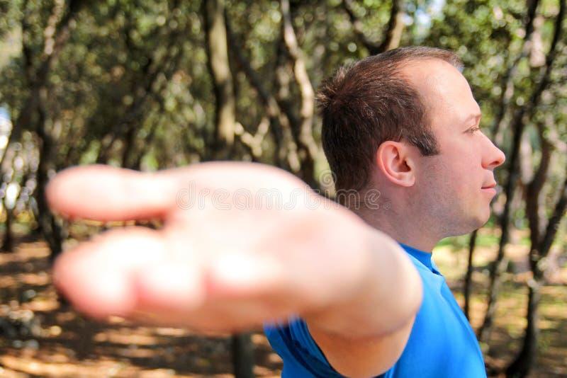 Красивый мышечный молодой человек делает протягивающ тренировки в sportswear спортсмена леса нося в природе ландшафта внешней стоковое фото rf
