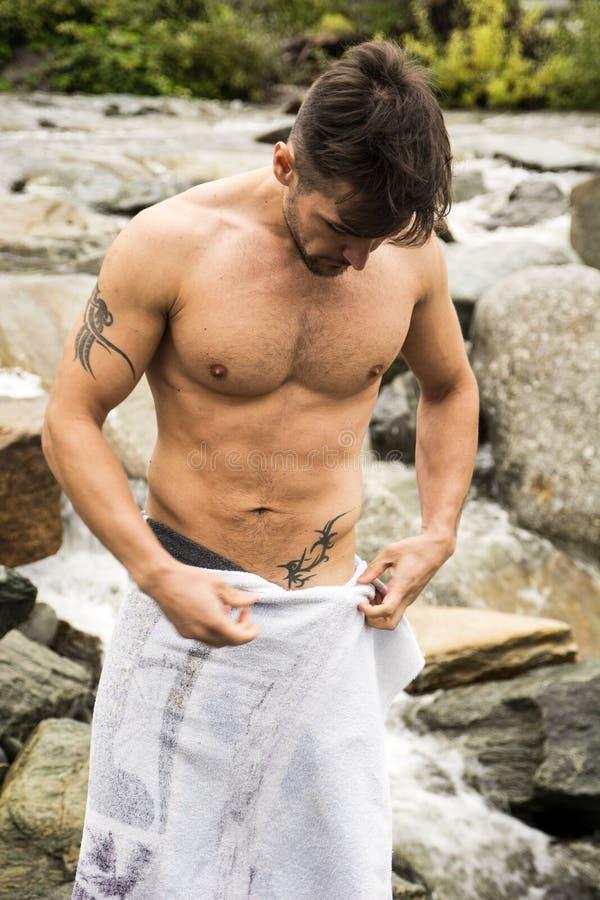 Красивый мышечный молодой человек внешний носящ только полотенце стоковые фотографии rf