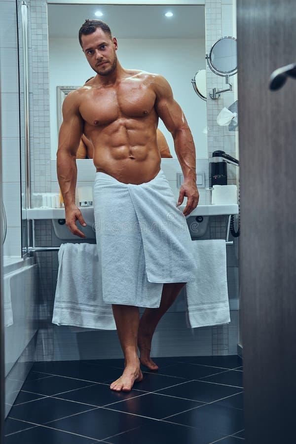Красивый мышечный мужчина в стильной двойной ванной комнате стоковые изображения rf