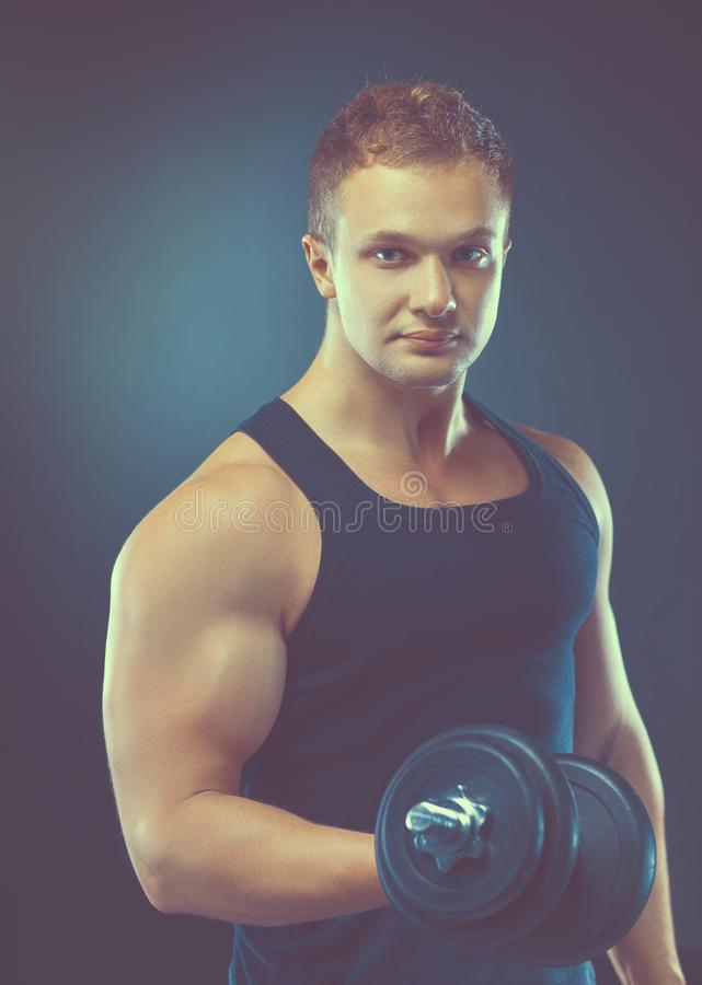 Красивый мышечный человек разрабатывая с гантелями стоковые фото