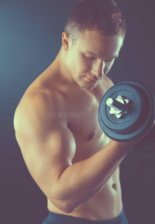 Красивый мышечный человек разрабатывая с гантелями стоковые изображения