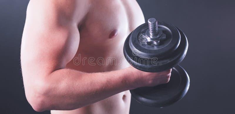 Красивый мышечный человек разрабатывая с гантелями стоковые фотографии rf
