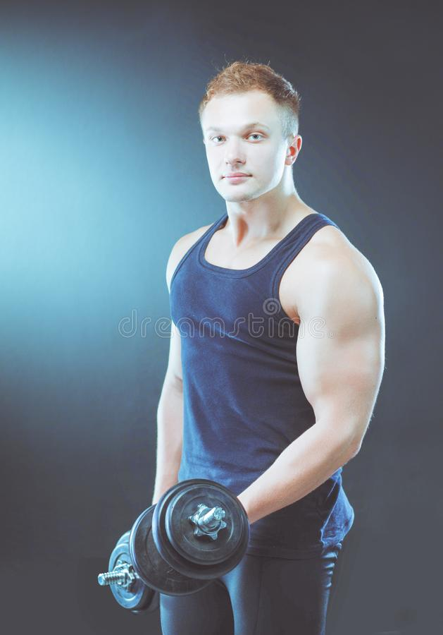 Красивый мышечный человек разрабатывая с гантелями стоковое фото