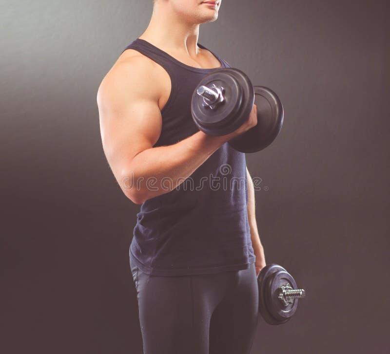 Красивый мышечный человек разрабатывая с гантелями стоковая фотография
