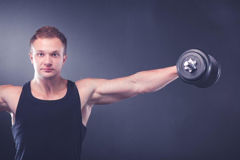 Красивый мышечный человек разрабатывая с гантелями стоковое изображение