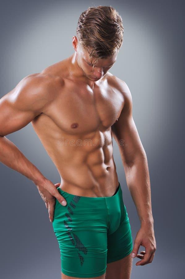 Красивый мышечный человек представляя на серой предпосылке стоковое фото