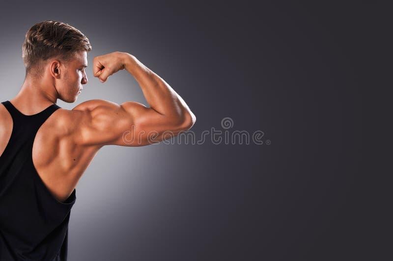 Красивый мышечный человек представляя на серой предпосылке стоковое изображение rf