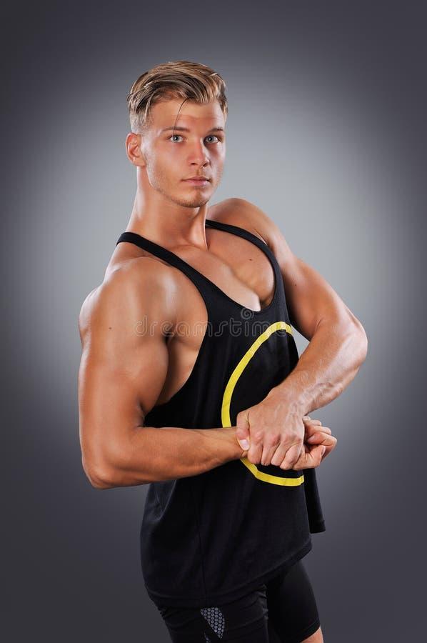 Красивый мышечный человек представляя на серой предпосылке стоковые фото