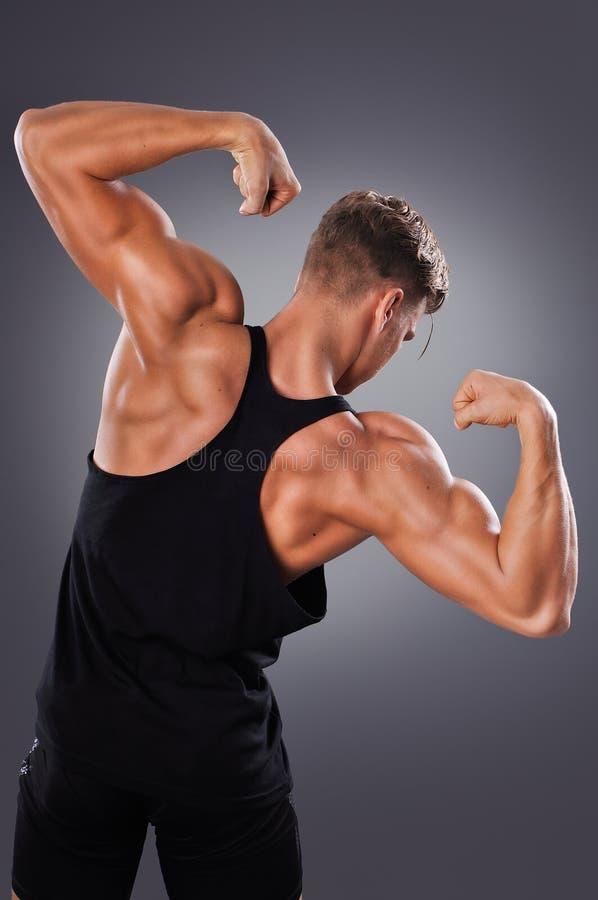 Красивый мышечный человек представляя на серой предпосылке стоковые фотографии rf