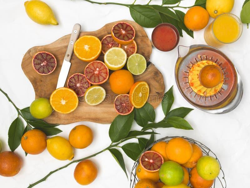 Красивый натюрморт с цитрусовыми фруктами на предпосылке белой бумаги и деревянной доске и ноже стоковое изображение rf