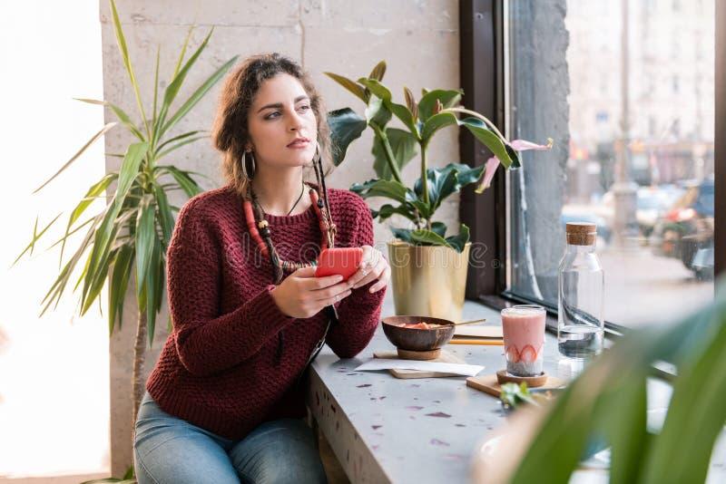 Красивый носить фрилансера темный - красный свитер и ожерелье имея обед стоковое фото