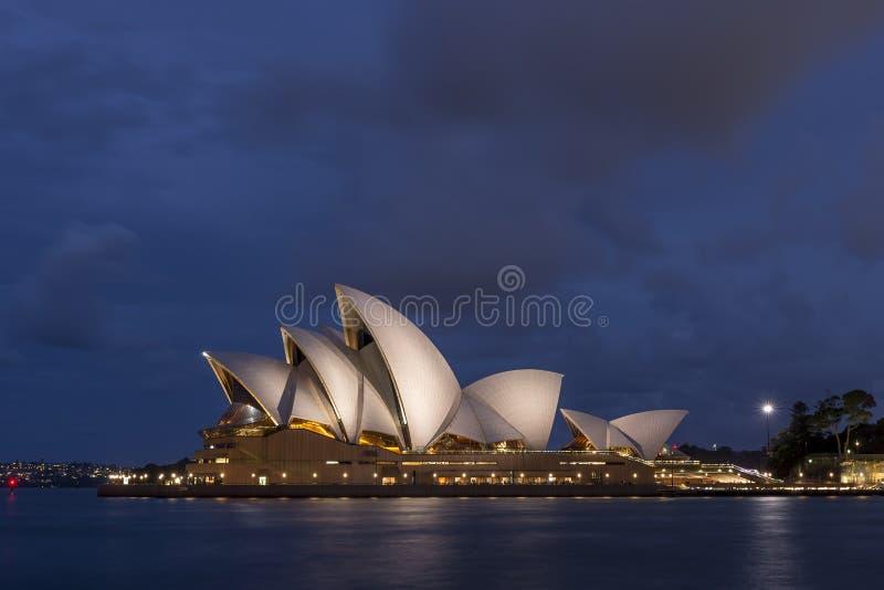 Красивый оперный театр Сиднея освещенный голубым светом часа, Австралией стоковые изображения