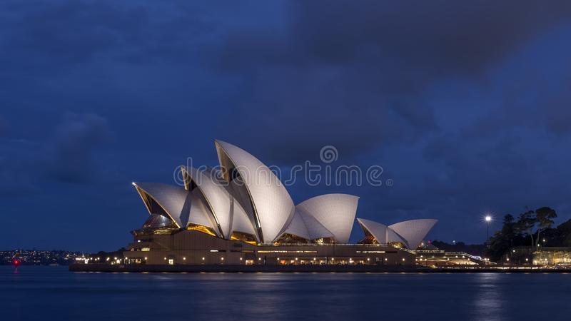 Красивый оперный театр Сиднея освещенный голубым светом часа, Австралией стоковые фото