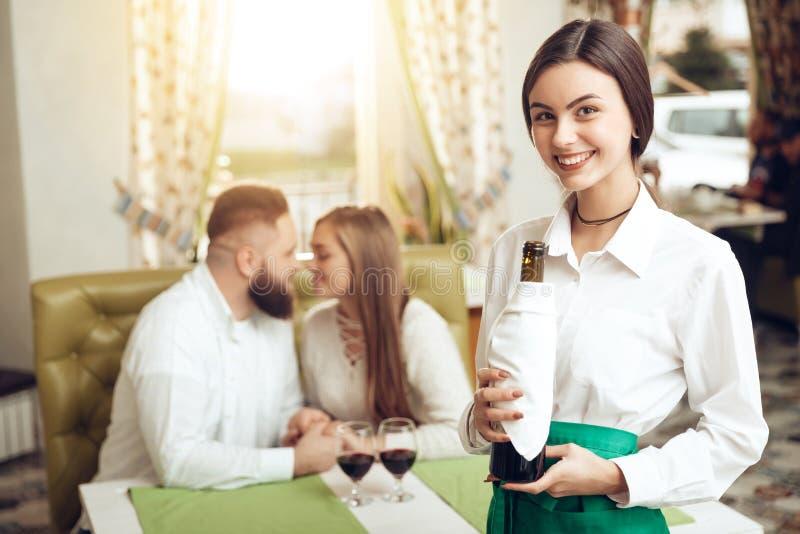 Красивый официант девушки держит открытую бутылку вина стоковая фотография
