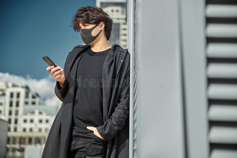 Красивый парень в медицинской маске лица, используя смартфон на улице стоковая фотография rf