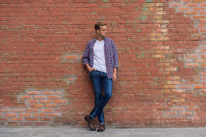 Красивый парень стоя близко кирпичная стена стоковая фотография