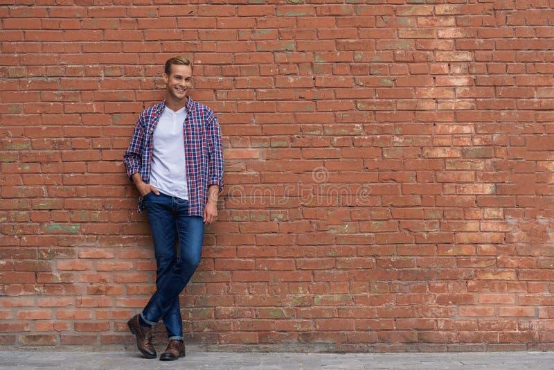 Красивый парень стоя близко кирпичная стена стоковые изображения