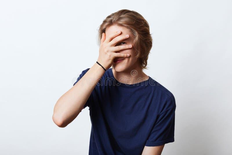 Красивый парень с привлекательным возникновением, прячущ его сторону с рукой, смотрящ через пальцы, имеющ застенчивое выражение М стоковые изображения rf