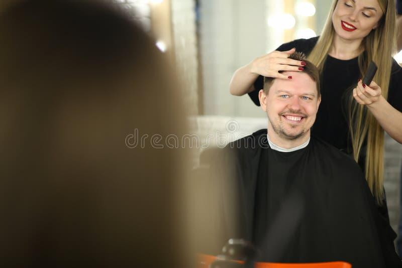 Красивый парикмахер делая стиль причесок клиента человека стоковое фото