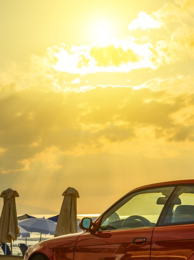 Красивый пасмурный заход солнца Крит, Европа Яркое небо над автомобилем Зонтики пляжа на предпосылке стоковые изображения