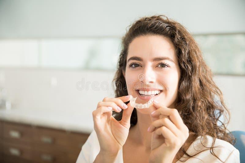 Красивый пациент держа ортодонтические стопорные устройства в зубоврачебной клинике стоковое фото rf