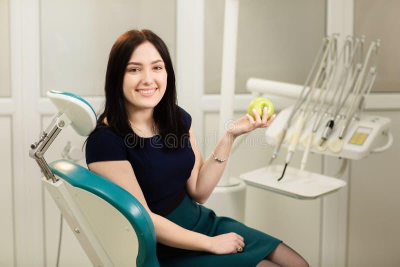 Красивый пациент женщины сидя в зубоврачебном оборудовании и владениях предпосылки кресла яблоко стоковое изображение rf