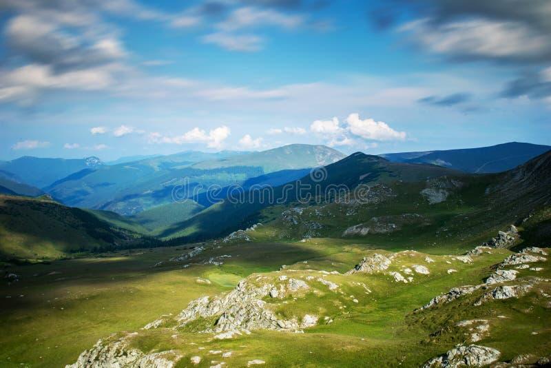 Красивый пейзаж горы Драматическое, голубое небо с много облаков Высоты гор покрытых с зеленой травой и стоковое фото rf
