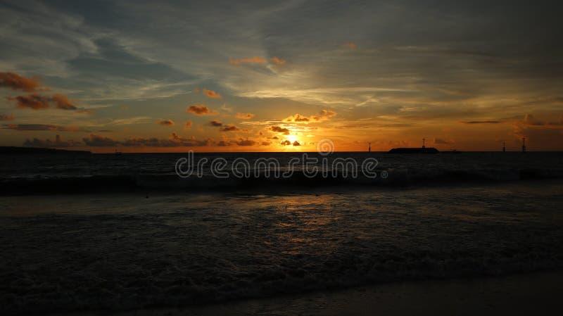 Красивый пейзаж на пляже с заходом солнца и облаками в Бали, Индонезии стоковая фотография rf
