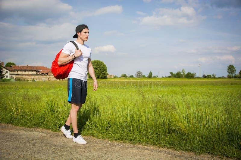 Красивый пеший туризм молодого человека внешний на сельской дороге стоковое фото rf