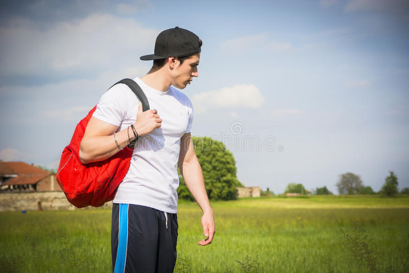 Красивый пеший туризм молодого человека внешний на сельской дороге стоковые фото