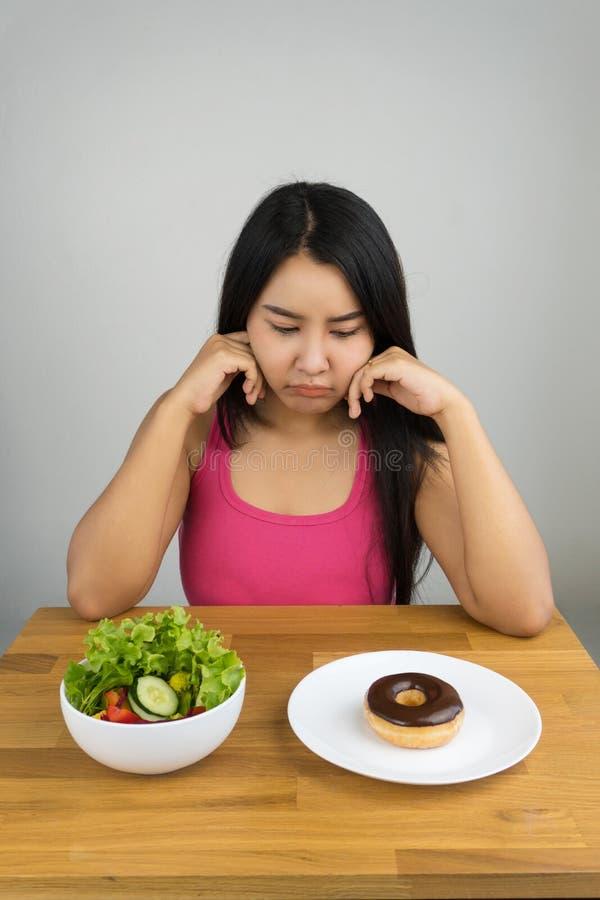 Красивый плюс женщина размера азиатская выбирая между салатом и донутом шоколада стоковая фотография rf