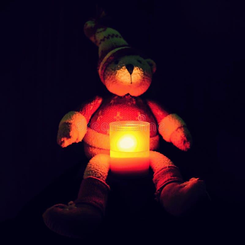 Красивый плюшевый медвежонок рождества сидя с свечой Сезонная предпосылка зимы на рождество и праздники Черная чистая предпосылка стоковая фотография