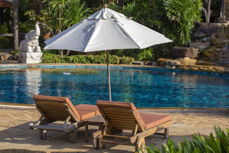 Красивый пляж с бассейном, пальмами, кушетками и зонтиком в тропическом саде около моря стоковые изображения