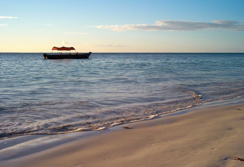 Красивый пляж с малой рыбацкой лодкой на пляже Michamvi, Занзибаре стоковые фото