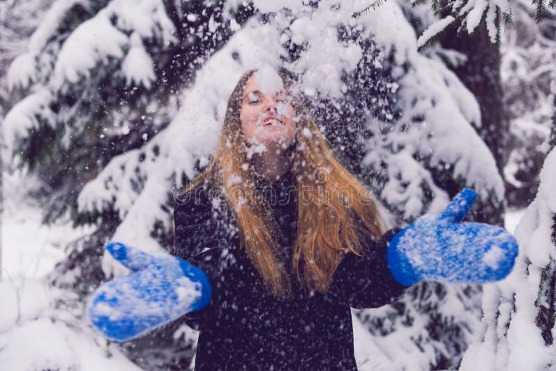 Красивый портрет девушки в женщине леса зимы усмехаясь играя в снеге стоковое фото
