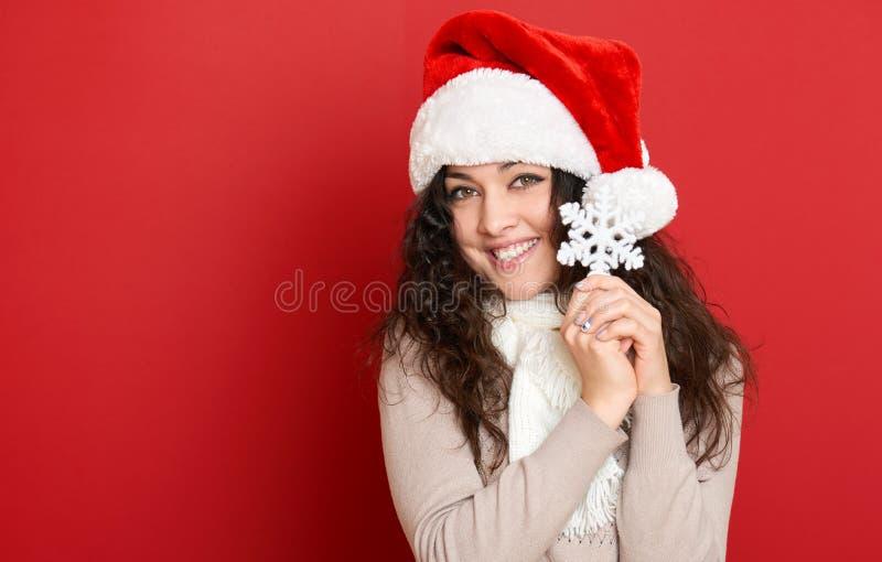 Красивый портрет молодой женщины в шляпе хелпера santa при большая снежинка представляя на красном цвете стоковое фото rf