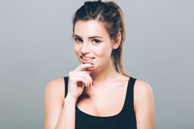 Красивый портрет молодой женщины усмехаясь представляющ привлекательное белокурое стоковые изображения