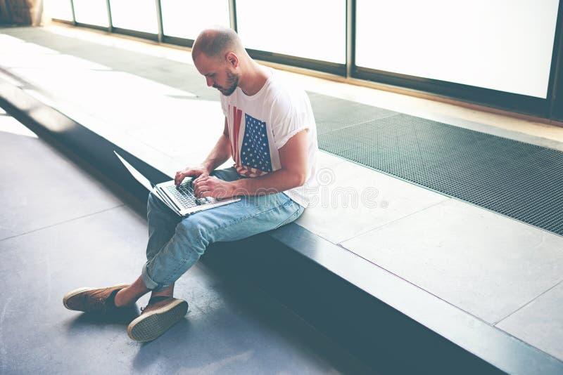 Красивый подросток изучая на его портативном компьютере пока сидящ в зале университета стоковое изображение