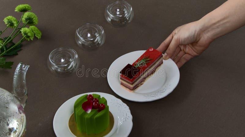 Красивый прозрачный чайник чайника с вкусным зеленым черным чаем с яблоком, с свечами и с десертом в стоковые изображения