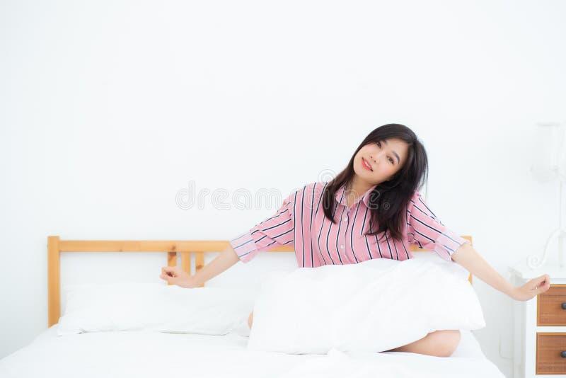 Красивый простирания женщины портрета молодого азиатского и ослабить в кровати после бодрствования вверх по утру на спальне стоковая фотография rf